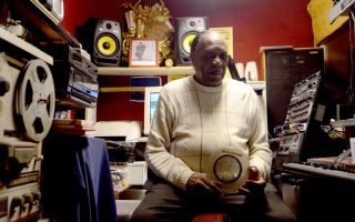"Charlie McClendon in his home studio with the original reel-to-reel recording of ""Rainy Night in Georgia."" photo by pat Jarrett."