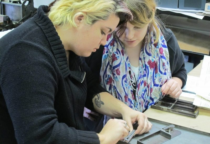 <p>Two Sweet Briar College students, Katie Holloway and Sally Toms, learn to set movable type at the Virginia Arts of the Book Center.>