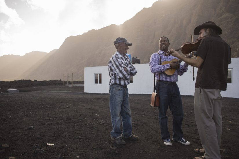 Zerui Depina (center) plays the cavaquinho and Danny Knicely (right) on fiddle in Chã das Calderas, Fogo, in Cabo Verde. Frankie Centeio (left) looks on. Photo by Pat Jarrett/Virginia Folklife Program.