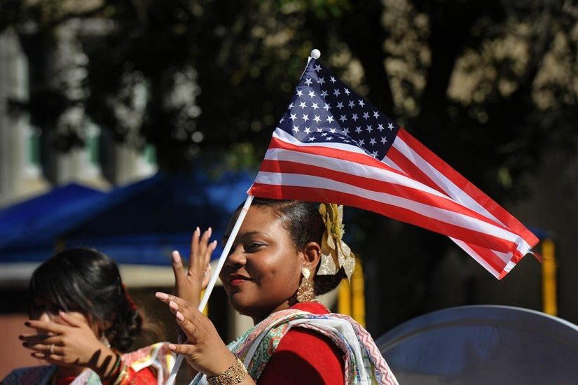 A woman waves an American flag at the Prio Bangla festival in Arlington. A recent grant from VA Humanities will fund an interpretive publication, to be distributed in conjunction with the festival, featuring interviews with more than a dozen immigrants and refugees. Photo Courtesy © Lloyd Wolf / Columbia Pike Documentary Project